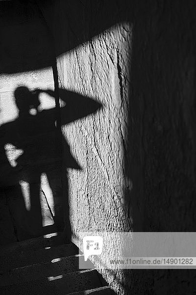 Shadow of a tourist standing and taking a picture with sunlight and shadows cast on the wall and steps; Cordoba  Cordoba Province  Spain