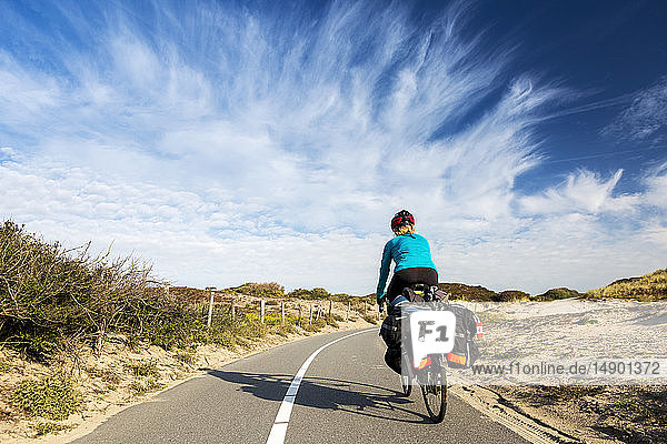 Female cyclist on paved bike pathway along rolling sand dunes with dramatic clouds and blue sky  South of Zandvoort; Netherlands