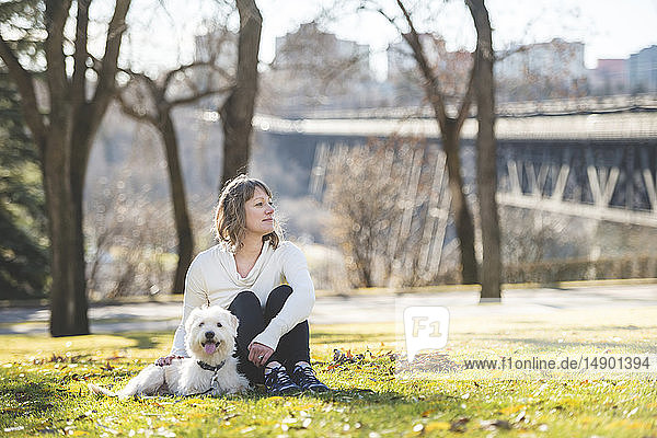 Woman sitting on the grass in a park with her dog with a city skyline in the background; Edmonton  Alberta  Canada