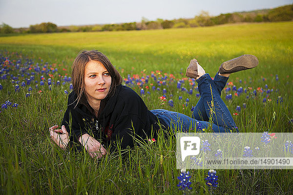A young woman laying in a field of bluebonnet wildflowers; Waco  Texas  United States of America