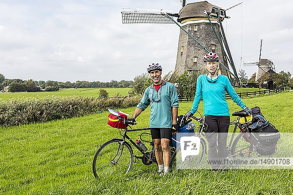 Female and male cyclists on grassy hill with two old wooden windmills in the background  near Stompwijk; Netherlands