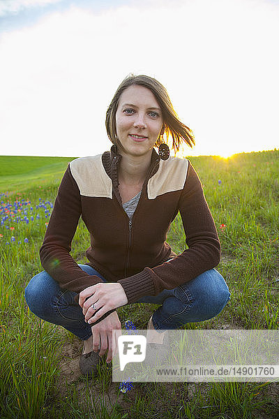 Portrait of a young woman in a meadow with wildflowers at sunset; Waco  Texas  United States of America