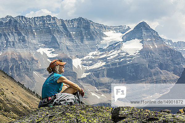 Female hiker sitting on a rocky area overlooking mountain vista in the background; British Columbia  Canada