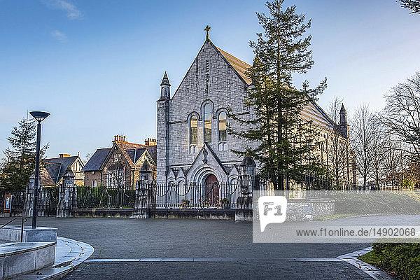 A stone church building along a quaint street; Ireland