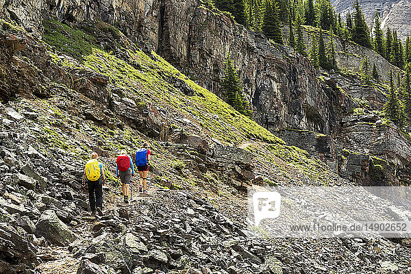 A group of female hikers along a rocky mountain pathway with rock cliffs in the background; British Columbia  Canada