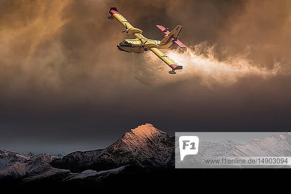 An aircraft dropping water on a forest fire in the mountains below  composite image