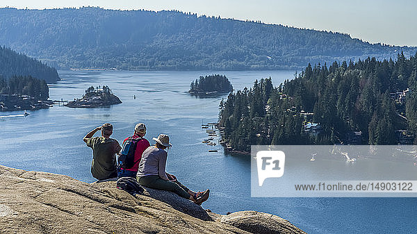 Hikers sitting at Quarry Rock on the Baden-Powell Trail looking out to the coastline  Deep Cove  North Vancouver; Vancouver  British Columbia  Canada