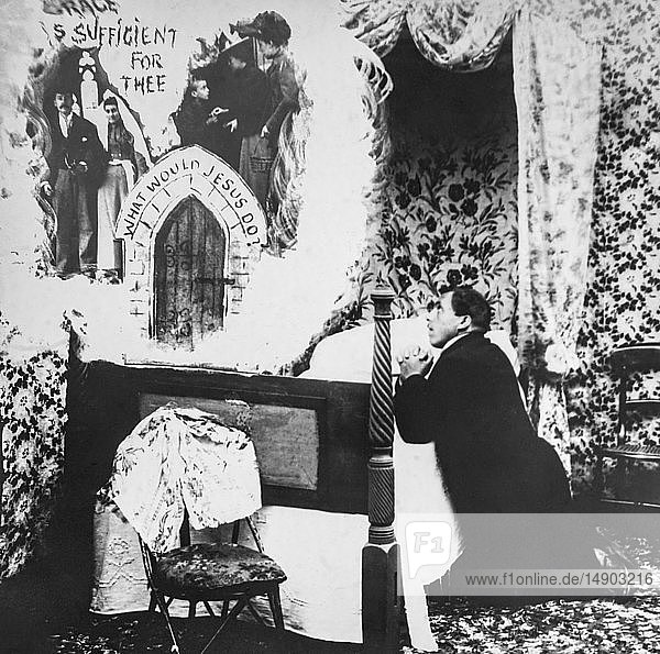 Magic lantern slide circa 1900.Victorian.Social History. Image from a slide presentation entitled In His step or In jesus Name. .Man on knees at bedside praying to God