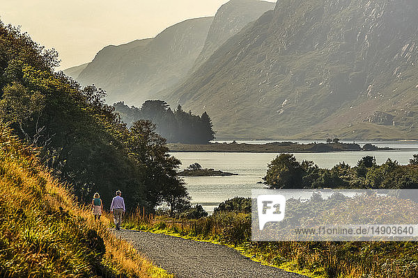 A couple walks down a trail on the water's edge in Glenveagh National Park; County Donegal  Ireland
