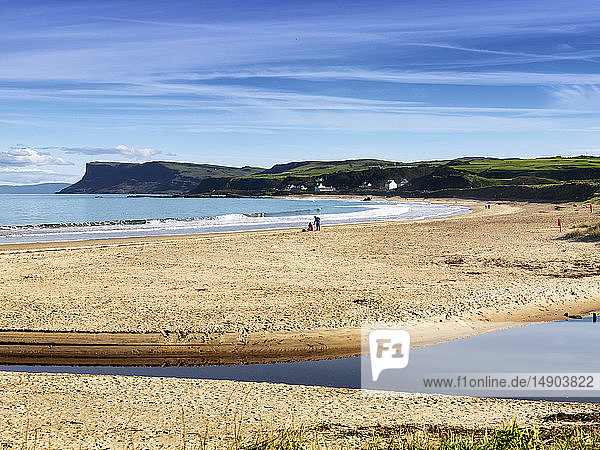 People enjoying the beach along the Atlantic coast with lush green landscape and cliffs in the distance; Ballycastle  county Antrim  Ireland