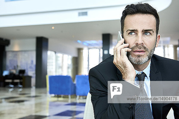 Businessman using smart phone while sitting on sofa