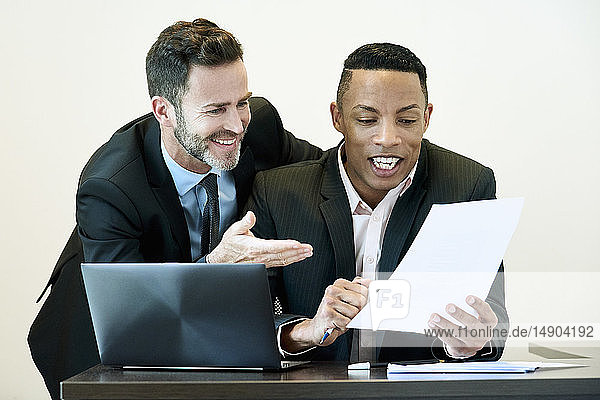 Businessmen discussing document at desk in office