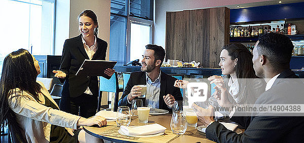 Waitress taking orders from business people in bar