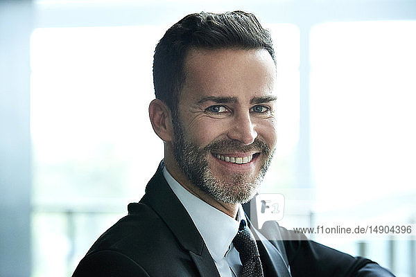 Portrait of smiling businessman standing in hotel lobby