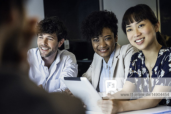 Smiling business people sitting in office