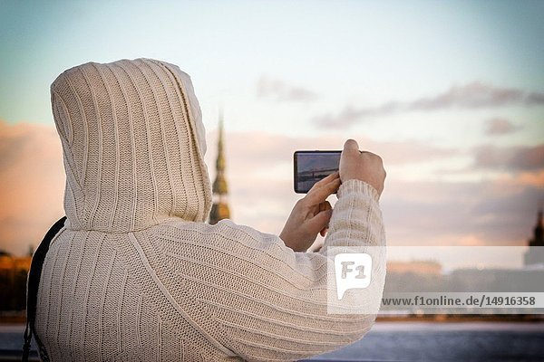 Man in white knitted jacket taking photo of cityscape with his smartphone in Riga  Latvia.