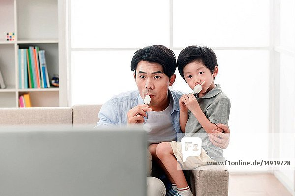 Happy father and son was watching TV.