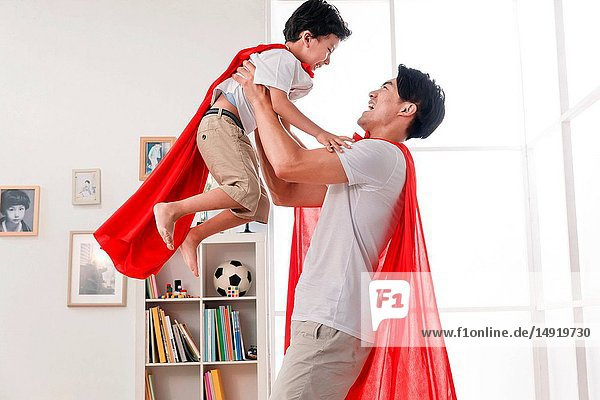 Happy father and son playing a superman