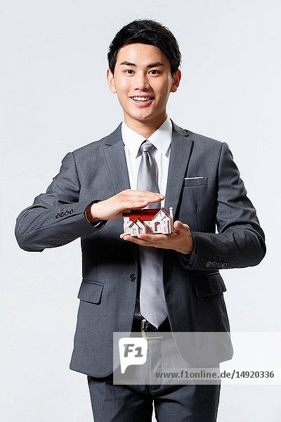 Business man holding a building model