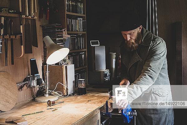 Bärtiger Mann mit schwarzer Mütze steht an der Werkbank in der Werkstatt und sägt ein Stück Holz.