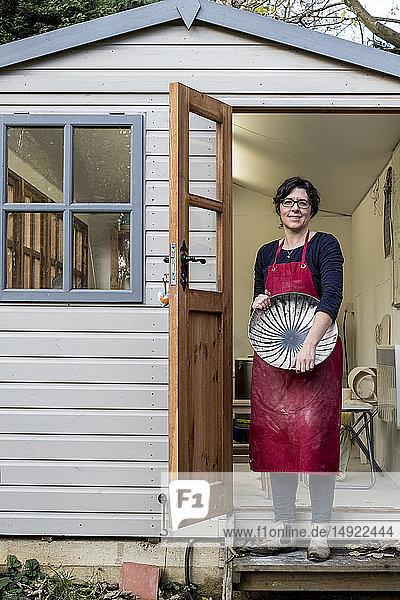 Frau mit roter Schürze  die auf Stufen vor ihrer Werkstatt steht und eine Keramikschale mit schwarzem Linienmuster hält.