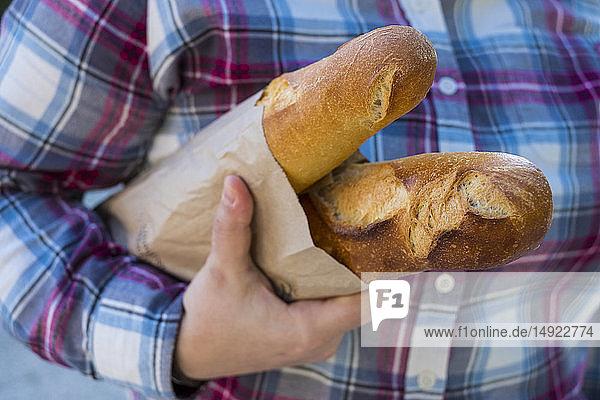Nahaufnahme einer Person  die zwei frisch gebackene französische Baguettes in einer braunen Papiertüte hält.