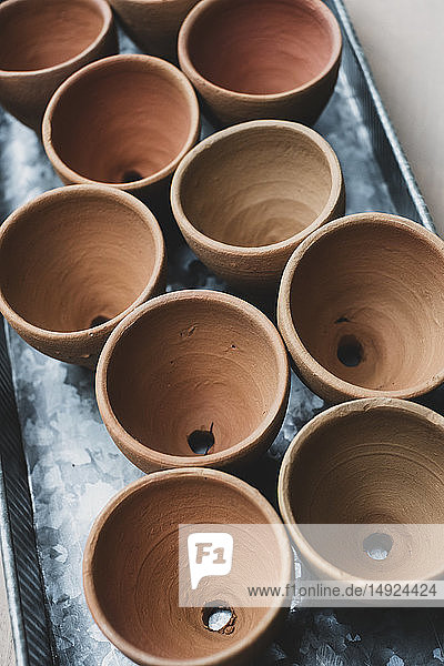 High angle close up of terracotta plant pots on metal tray.