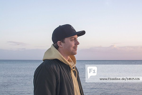 Profile shot of handsome smiling natural and casual looking male in late twenties with hood jacket and cap looks straight forward,  ocean horizon behind.