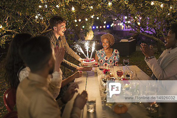 Happy friends celebrating birthday with sparkler cake at garden party table