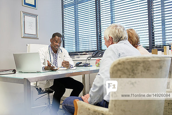 Doctor with digital tablet talking to senior couple in doctors office