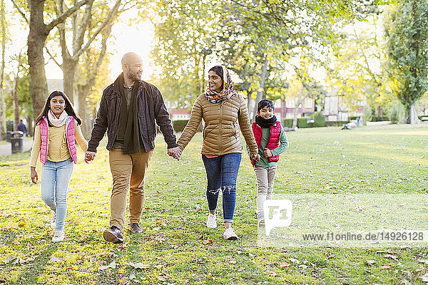 Muslim family holding hands  walking in sunny autumn park