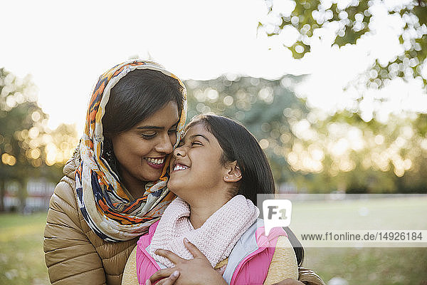 Affectionate  happy Muslim mother in hijab hugging daughter in autumn park