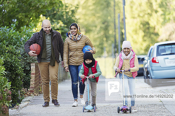 Muslim family watching and riding scooter on sidewalk