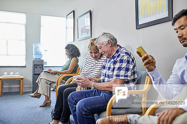 Senior couple using smart phone in clinic waiting room