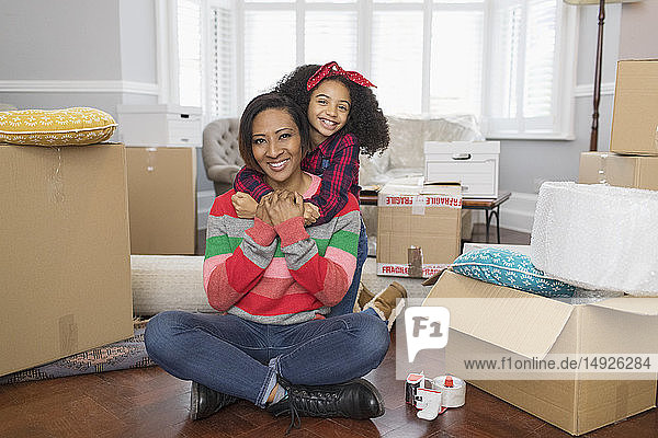 Portrait happy mother and daughter hugging  moving into new house