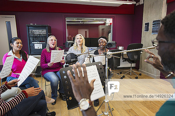 Male conductor leading womens choir with sheet music singing in music recording studio