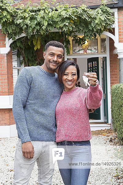 Portrait happy couple holding house keys outside new house