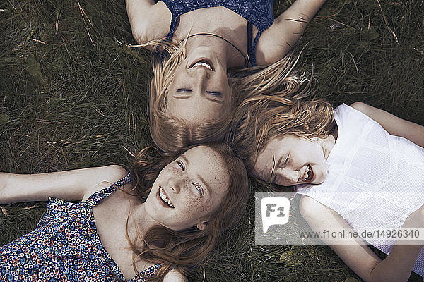 Portrait happy sisters laying in grass Portrait happy sisters laying in grass