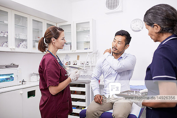 Male patient explaining shoulder pain to female doctor in clinic examination room