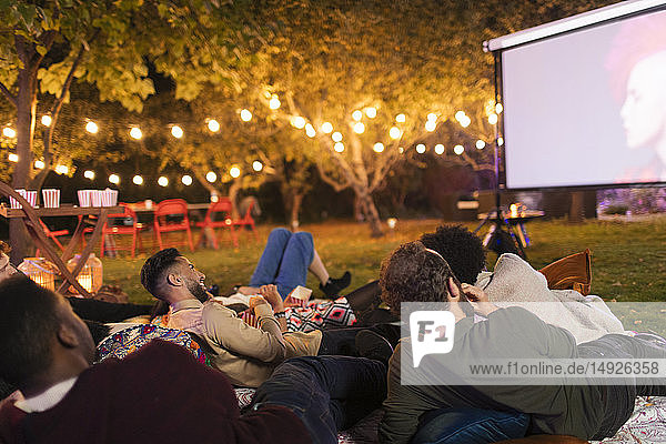 Friends relaxing  watching movie on projection screen in backyard