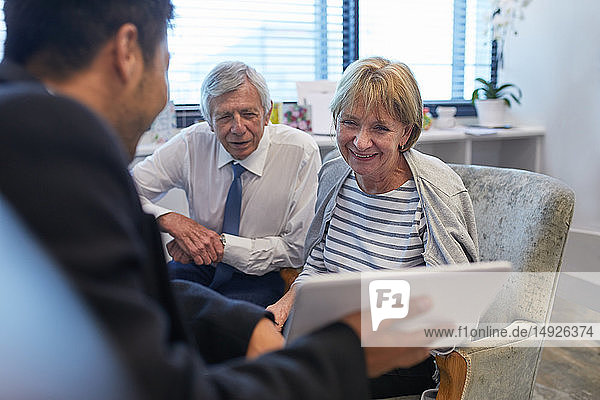 Doctor with digital tablet talking to senior couple in clinic doctors office