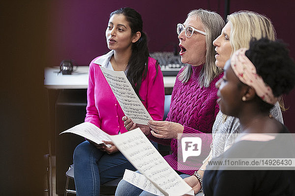Womens choir with sheet music singing in music recording studio
