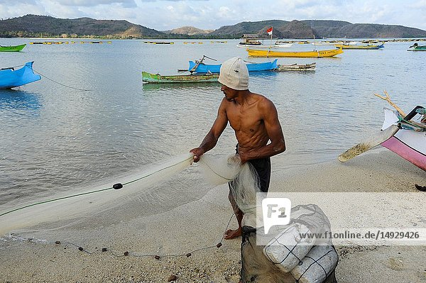 Lombok  West Nusa Tenggara  Indonesia  Asia - A local fisherman is cleaning his fishing net on a beach in South Lombok.