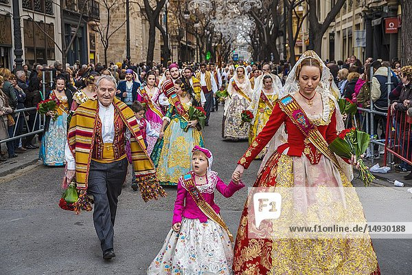 Fallas festival. Falleras in traditional dress. Parade to the Plaza de la Virgin in order to make an offering of flowers to Our Lady of the Forsaken  the Patron Saint of Valencia. The celebration takes place from 4 pm until past nightfall. With all of the bunches of flowers given by the falleras to the Virgin  an impressive 15 metre-high tapestry is formed on the main façade of the Basilica and a mantle is made for the Virgin. Valencia. Valencian Community. Spain.