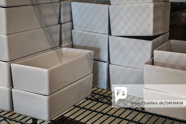 Stacks of white rectangle ceramic food containers on a metal wire rack.