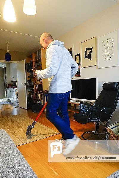 Stockholm  Sweden A man vacuums at home.