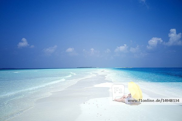 Young caucasian woman laying on the sandy beach with yellow umbrealla  Dharavandhoo  Baa Atoll  Maldives  Indian Ocean  South Asia.