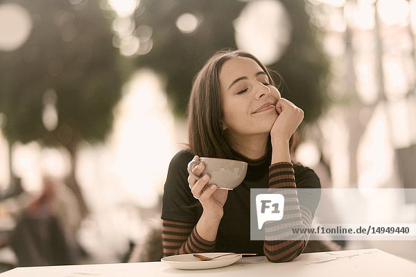 Portrait of pleased woman holding coffee cup while enjoying break at table in café  closed eyes  pure happiness  joy  in Munich  Germany