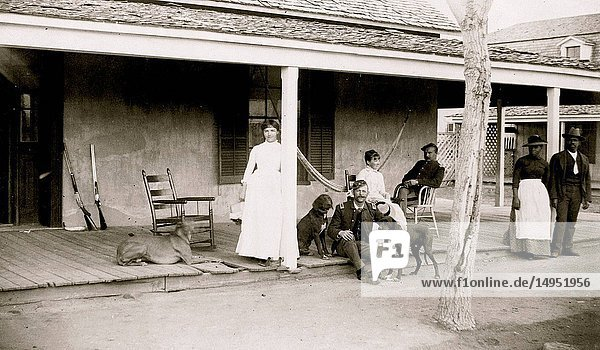 Two soldiers and two women on porch  with Afro-American woman and man to right  Fort Verde  Arizona