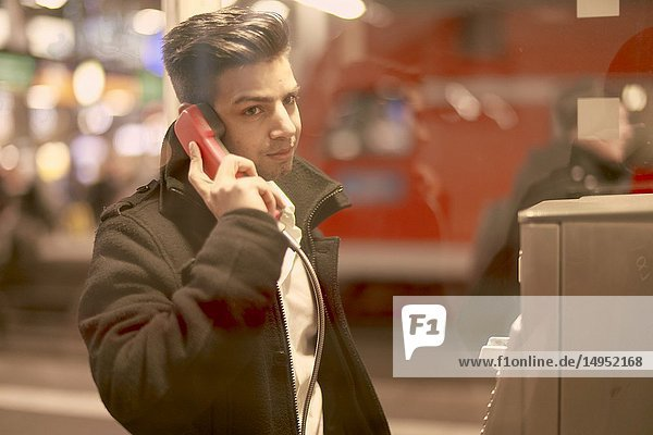 Young man using telephone cabin  Afghan ethnicity  in Munich  Germany.